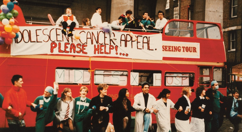 Youths fundraising around a red London bus