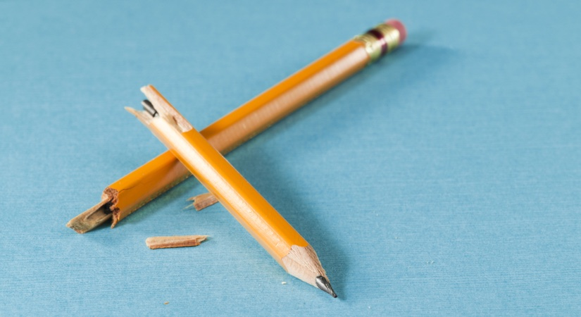 A broken pencil sitting on a blue table