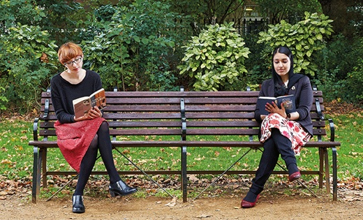 2 female students sit on a bench reading their books