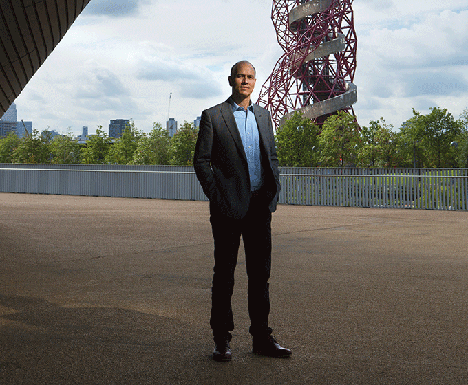 A man stands next to the ArcelorMittal Orbit in Stratford