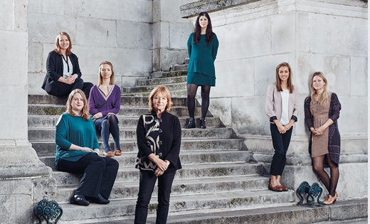 A group of female professionals at UCL, stand and sit on stairs and all smile at the camera