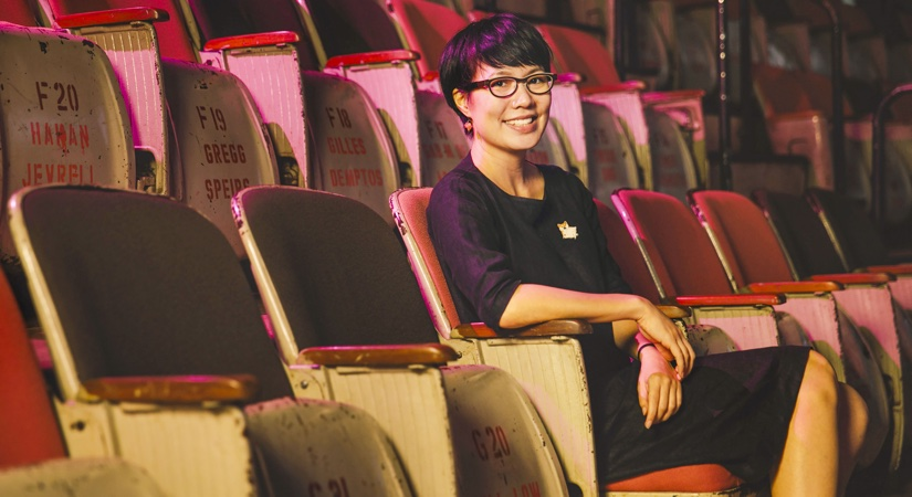 Sharon Tan UCL Alumni, sits on a row of chairs at her arthouse cinema in a Brutalist tower block in Singapore