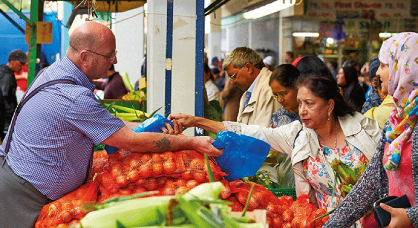 A lady handing over money to a worker at a fruit and veg stall at a bustling market
