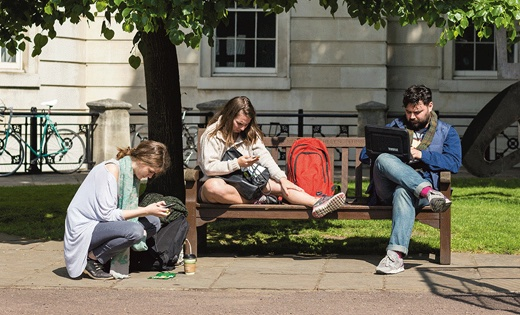 Students sit on a park bench glued to their phones and laptops