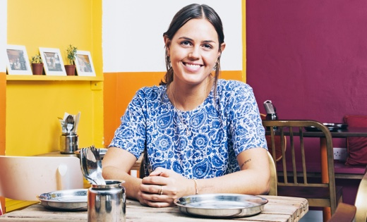 UCL graduate Grace Regan sits at a table in a restaurant