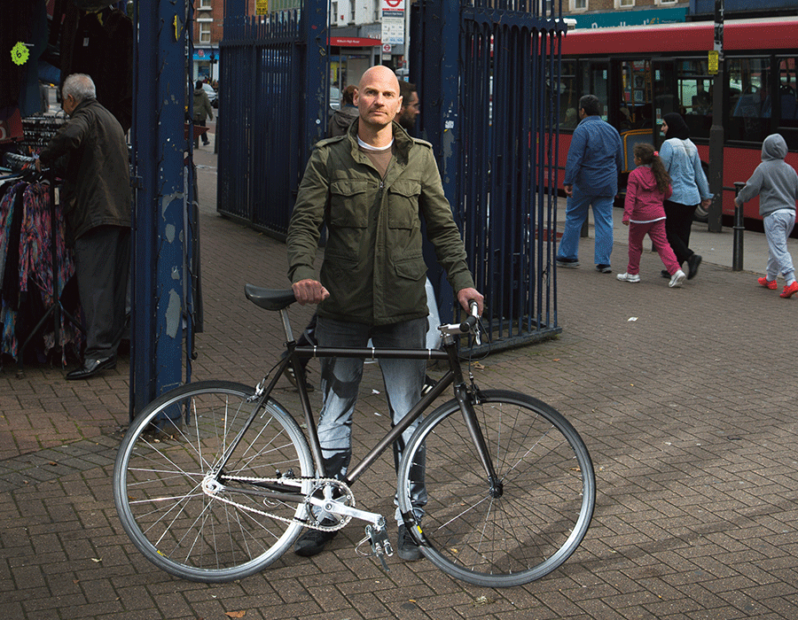 A man stands in the street posing with is bike