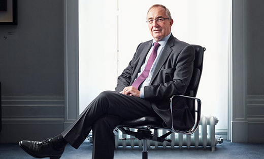 UCL President and Provost Professor Michael Arthur sitting in a chair smiling