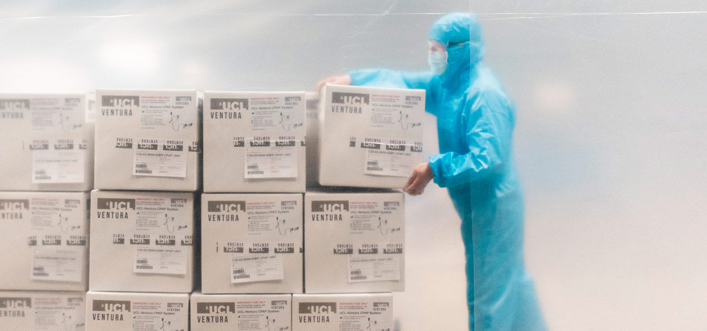 A person wearing a blue hazmat suit and a facemask carries boxes