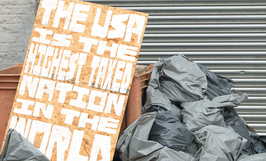 A placard dumped amongst a pile of rubbish with 'The USA is the highest taxed nation in the world' written on it