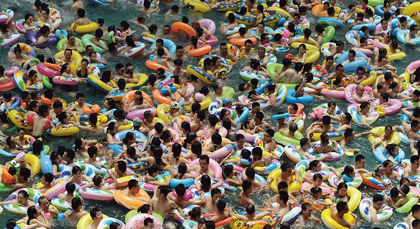 Large crowds swiming together with inflatables